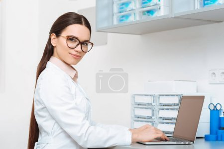 side view of smiling doctor in white coat looking at camera while working on laptop in clinic