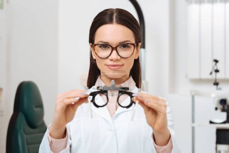 portrait of young optometrist in white coat showing trial frame in hands in clinic