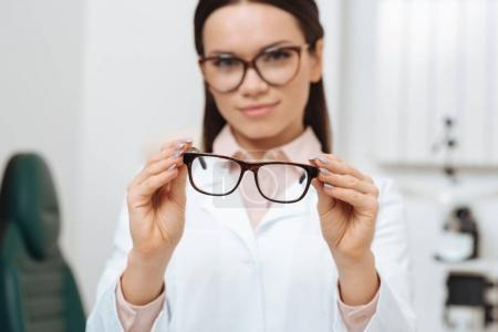 selective focus of ophthalmologist holding pair of eyeglasses in hands in clinic