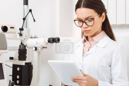 portrait of focused optometrist using digital tablet in clinic
