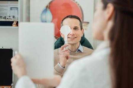 selective focus of smiling man getting eye examination by oculist in clinic
