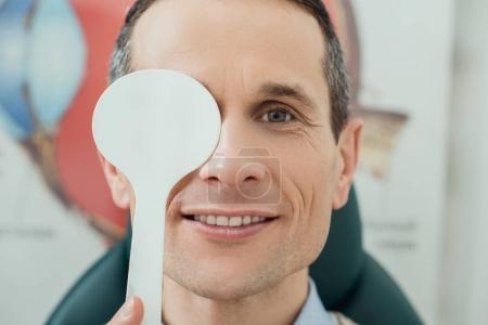 obscured view of smiling man getting eye test in clinic