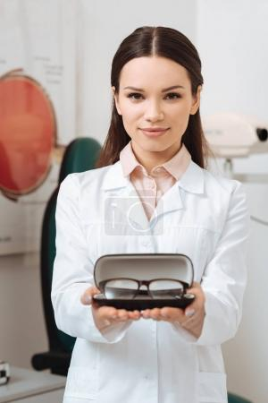 portrait of optician in white coat holding pair of eyeglasses in clinic