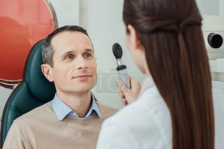 portrait of man getting eye test by ophthalmologist in clinic