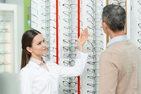 side view of smiling oculist pointing at eyeglasses on shelf in optics