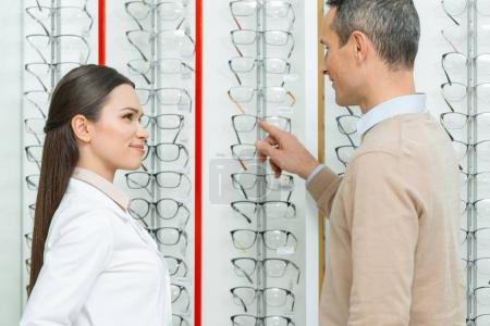 side view of man choosing pair of eyeglasses with oculist standing near by in optics