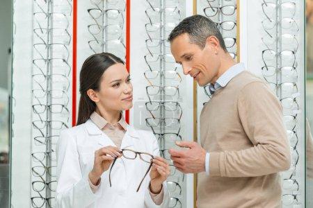 oculist helping man to choose pair of eyeglasses in optics