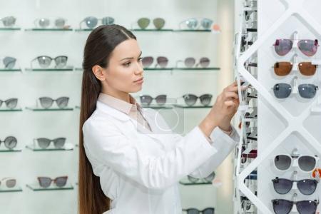 side view of optometrist taking eyeglasses from shelf in optics
