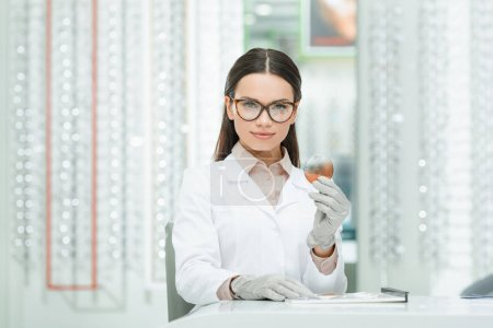 portrait of oculist in eyeglasses with lens in hand looking at camera in optics