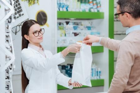 selective focus of smiling ophthalmologist giving purchase to patient in optics
