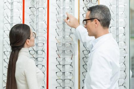 side view of oculist helping woman to choose pair of eyeglasses in optics