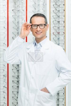 portrait of smiling oculist in eyeglasses standing in optics