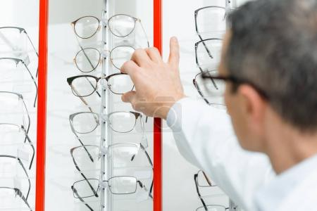 selective focus of optometrist taking eyeglasses from shelf in optics