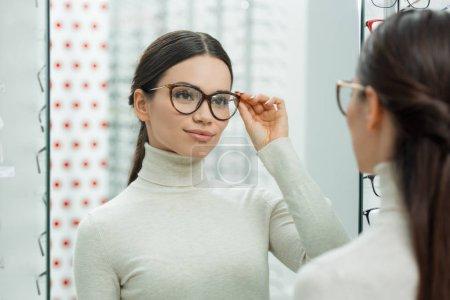 portrait of young smiling girl choosing pair of eyeglasses in optics
