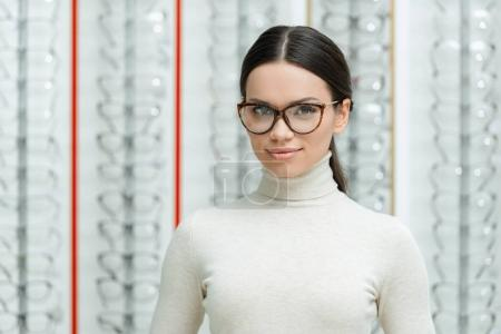 portrait of beautiful young woman in eyeglasses looking at camera in optics