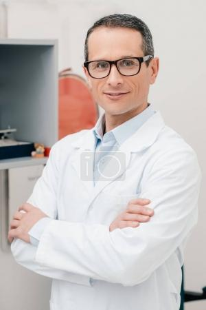 portrait of smiling doctor in eyeglasses with arms crossed looking at camera in clinic