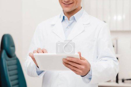 partial view of smiling doctor in white coat using digital tablet in clinic