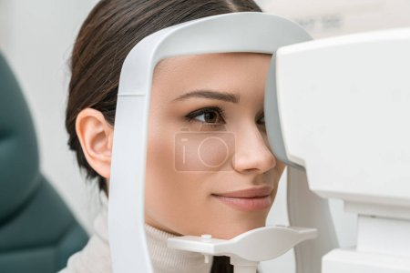 side view of young woman getting eye examination in slit lamp in clinic