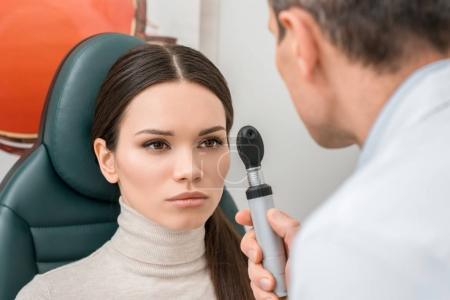 selective focus of young woman getting eye test by oculist in clinic