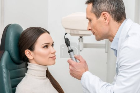 side view of patient getting eye test by oculist in clinic