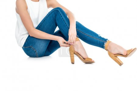 cropped view of girl in jeans wearing heels, isolated on white