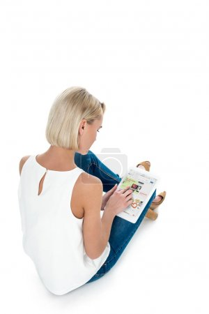 Back view of blonde woman using digital tablet with ebay app, isolated on white