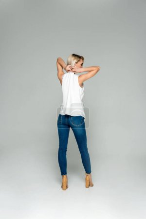 beautiful stylish woman taking off clothes, isolated on grey