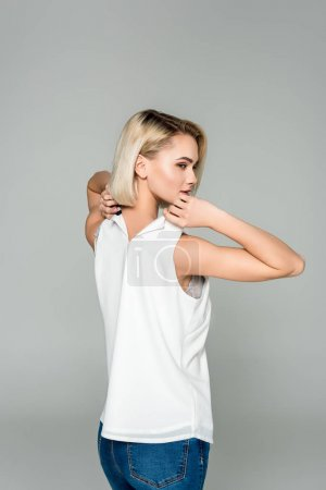 beautiful stylish woman undressing herself, isolated on grey