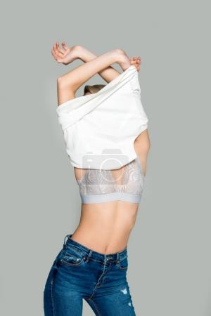 slim woman in bra taking off clothes, isolated on grey