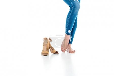 cropped view of barefoot woman standing near heels, isolated on white