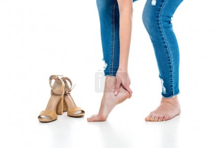 cropped view of tired barefoot woman standing near heels, isolated on white