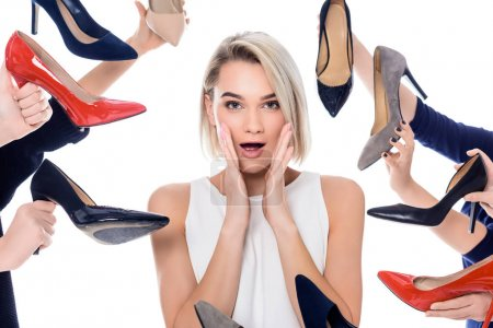 Photo for Shocked girl and lots of hands holding trendy heeled shoes, isolated on white - Royalty Free Image