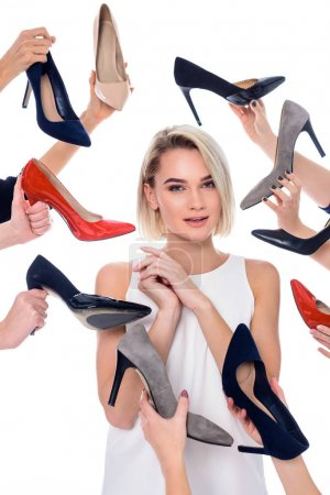 beautiful girl and lots of hands holding stylish heeled shoes, isolated on white