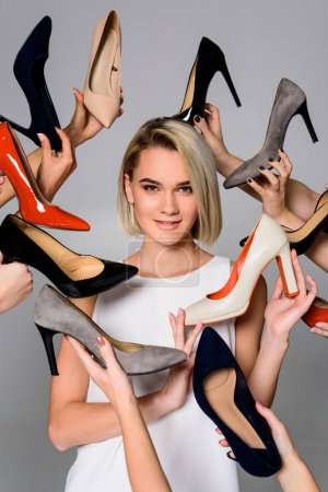 attractive woman and lots of hands holding trendy heeled shoes, isolated on grey