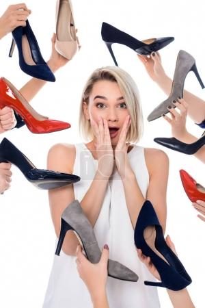 surprised girl and lots of hands holding trendy heels, isolated on white
