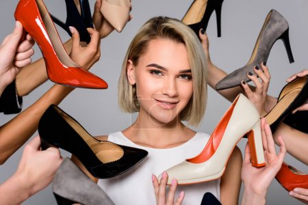 blonde girl and lots of hands holding stylish heels, isolated on grey