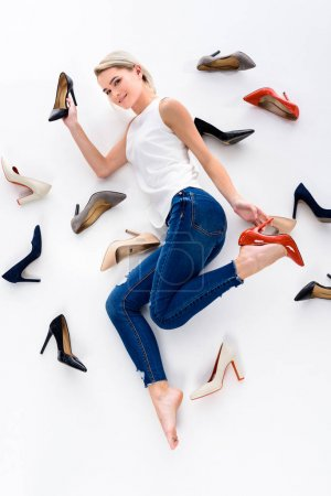 Photo for Beautiful woman posing with many heeled shoes, isolated on white - Royalty Free Image