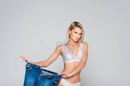 beautiful slim girl in lingerie holding big jeans, isolated on grey