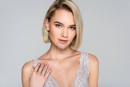sensual blonde woman posing in lace bra, isolated on grey