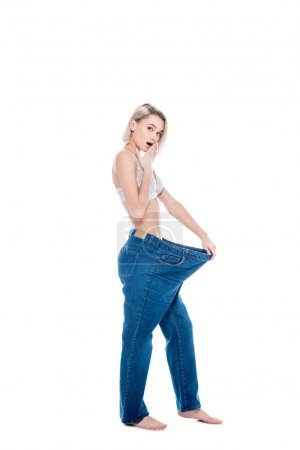 shocked slim girl in old jeans old jeans after losing weight, isolated on white