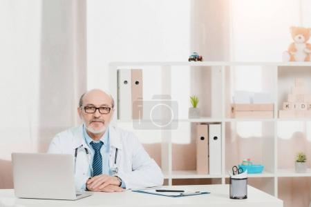 portrait of senior doctor in eyeglasses looking at camera while sitting at workplace with laptop in clinic