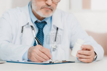 Photo for Partial view of doctor with pills in hand making notes on notepad at workplace - Royalty Free Image