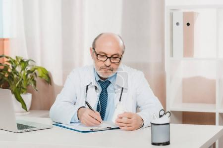 portrait of focused senior doctor making notes on notepad at workplace with laptop in clinic