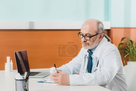 side view of focused senior doctor making notes on notepad at workplace with laptop in clinic