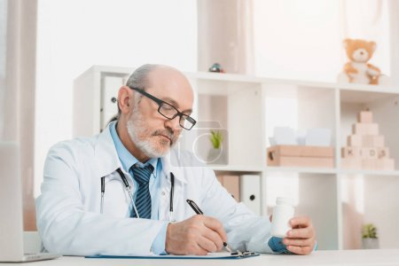 portrait of focused senior doctor making notes on notepad at workplace in clinic