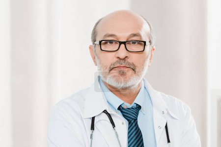 portrait of senior doctor in eyeglasses with stethoscope looking at camera