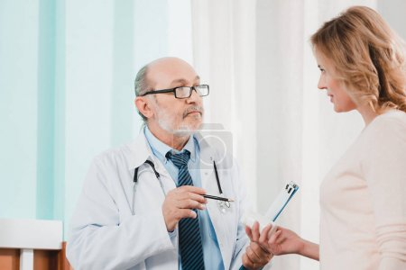 side view of senior doctor and female patient with medicines in hand in clinic
