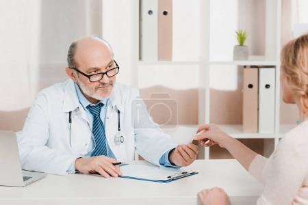 partial view of senior doctor giving prescription to patient at workplace in clinic