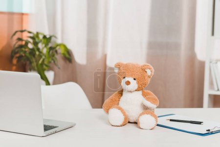 Photo for Close up view of laptop, teddy bear and notepad at doctors workplace in clinic - Royalty Free Image