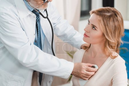 senior doctor in white coat examining woman with stethoscope in clinic
